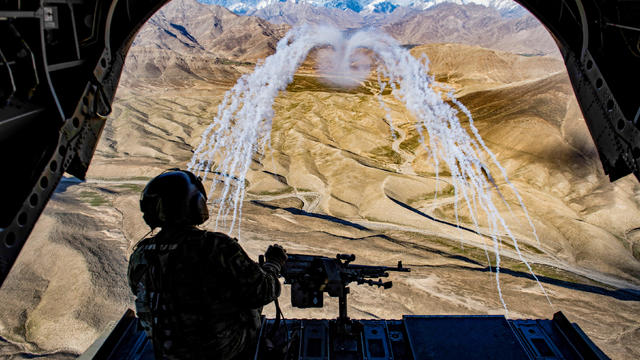FILE PHOTO: A U.S. Army crew chief flying on board a Chinook helicopter observes the successful test of flares during a training flight in Afghanistan