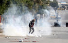 Tear gas is seen as protesters clash with riot police attempting to disperse the crowd during demonstrations, in Kasserine