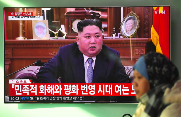 A woman walks past a television screen showing a New Year's speech by North Korean leader Kim Jong Un at a railway station in Seoul on Jan. 1, 2019.