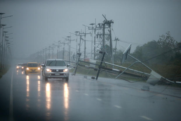Cars and fallen electricity poles are seen along a road as tropical storm Pabuk approaches the southern province of Nakhon Si Thammarat