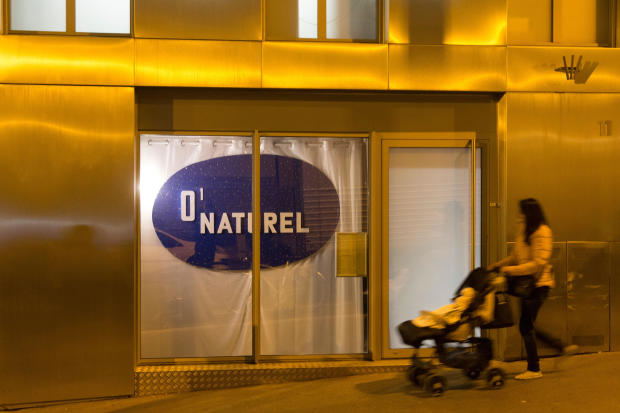 "A woman pushes a stroller past the nudist restaurant O'Naturel"" in Paris on Dec. 5, 2017."