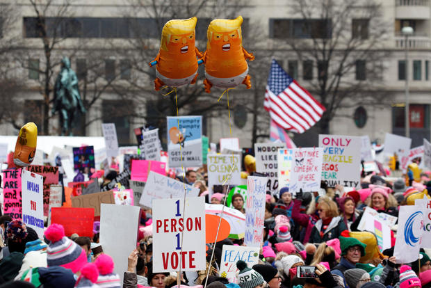 Baby Trump balloons float over thousands of people as they participate in the Third Annual Women's March at Freedom Plaza in Washington