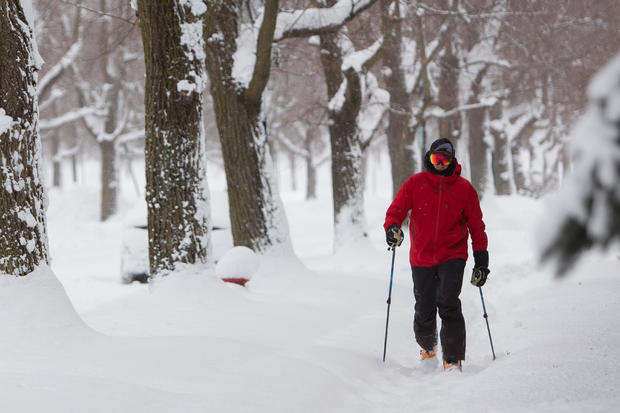 Man cross-country skis down sidewalk during a winter storm in Buffalo, New York