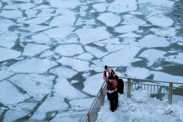 A pedestrian stops to take a photo by Chicago River as bitter cold phenomenon called the polar vortex has descended on much of the central and eastern United States