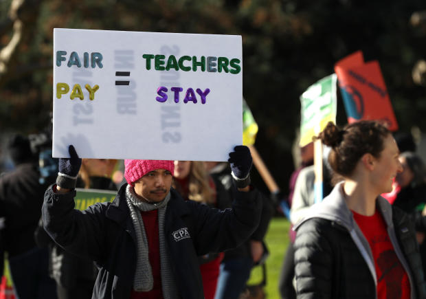 Oakland Unified School District students and teachers carry signs as they picket outside of Oakland Technical High School on Feb. 21, 2019, in Oakland, California.