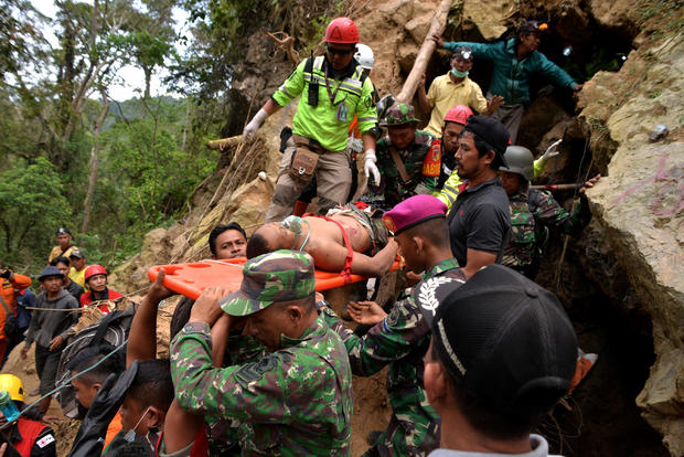 Rescue workers carry a miner who survived from the collapse of an illegal gold mine at Bolaang Mongondow regency in North Sulawesi