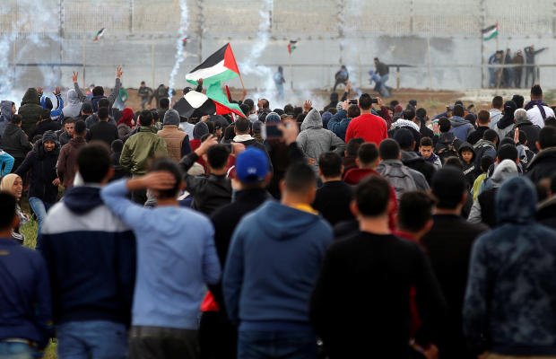 Palestinians gather as tear gas is fired by Israeli forces during a protest marking Land Day and the first anniversary of a surge of border protests, at the Israel-Gaza border fence east of Gaza City