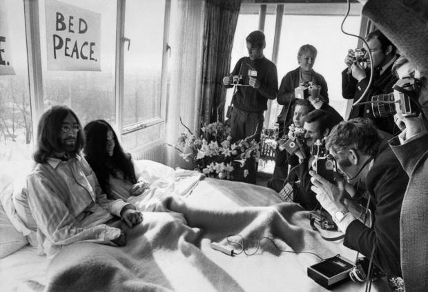 Beatles member John Lennon and his wife Yoko Ono receive journalists in their bedroom at the Hilton hotel in Amsterdam during their honeymoon in Europe March 25, 1969.
