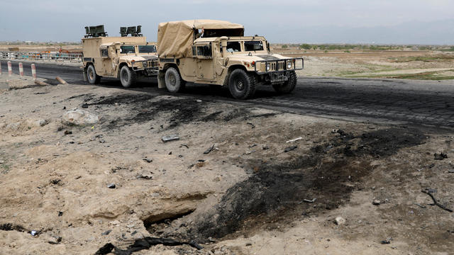 Afghan military convy past the site of a car bomb attack where U.S soldiers were killed near Bagram air base, Afghanistan