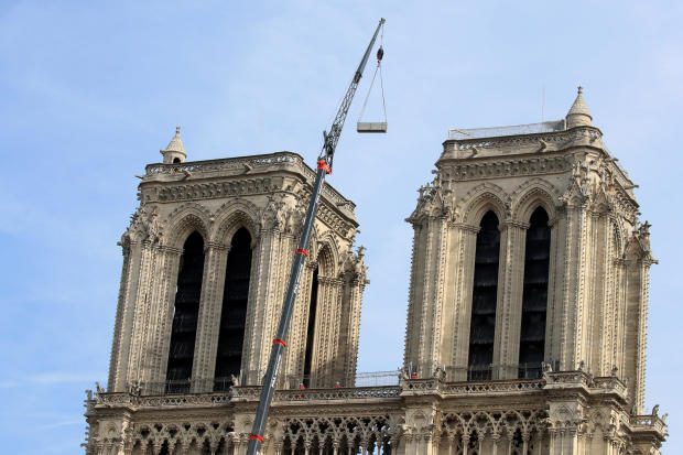 A crane works between the two towers at Notre Dame Cathedral days after a massive fire devastated large parts of the Gothic structure in Paris, France, April 18, 2019.