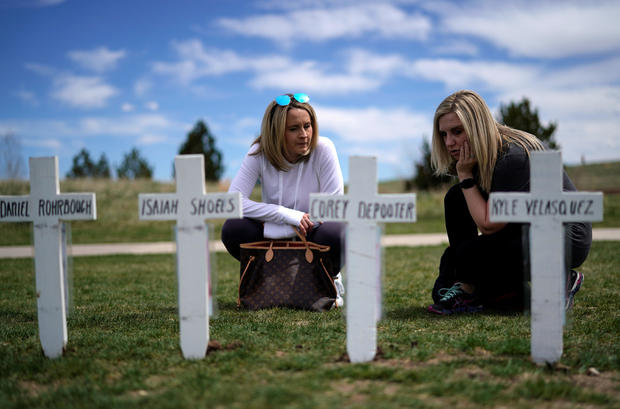Jennifer Dunsmore (L) and Cassanda Sadusky look at a line of crosses commemorating those killed in the Columbine High School shooting on the 20th anniversary of the attack in Littleton