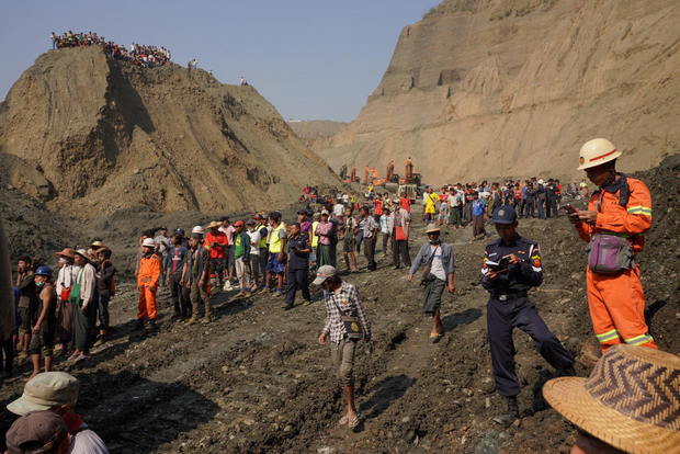Local people look on in a jade mine where the mud dam collapsed in Hpakant