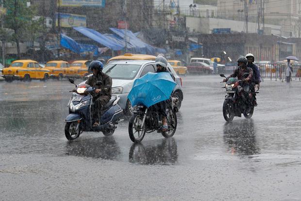 People ride their motorbikes during heavy rains in Kolkata