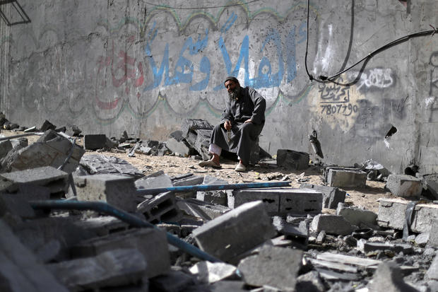 Palestinian man sits on debris near a building that was destroyed by Israeli air strikes, in Gaza City