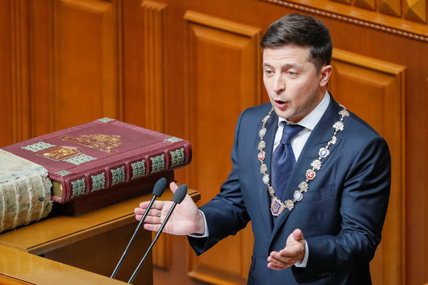 Ukraine's new President Volodymyr Zelenskiy applauds after taking the oath of office during his inauguration ceremony in the parliament hall in Kiev