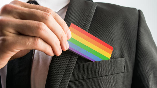 Man withdrawing wooden card painted as the gay pride flag