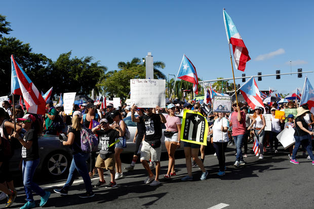 People chant slogans as they wave Puerto Rican flags during ongoing protests calling for the resignation of Governor Ricardo Rossello in San Juan