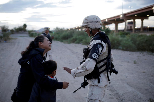 Guatemalan migrant Ledy Perez embraces her son Anthony while asking a member of the Mexican National Guard to let them cross into the United States from Ciudad Juarez, Mexico, July 22, 2019.