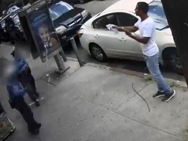 A man throws water at two New York Police Department traffic enforcement agents in the Queens borough of New York City July 24, 2019, in an image capture of surveillance video released by the NYPD Crime Stoppers Program.