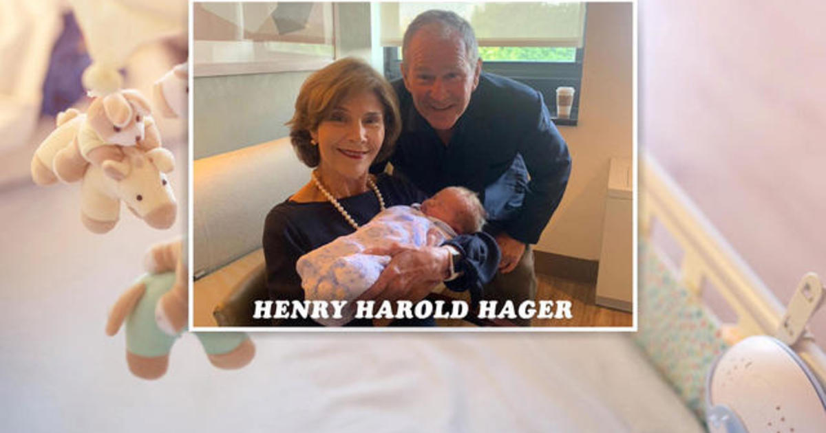 Former President George W. Bush shows pictures of first grandson