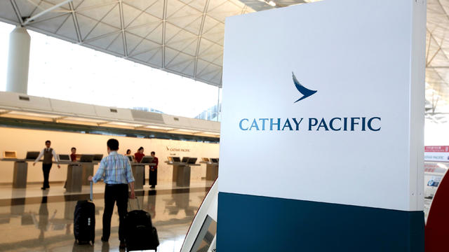 A passenger walks to the First Class counter of Cathay Pacific Airways at Hong Kong Airport in Hong Kong