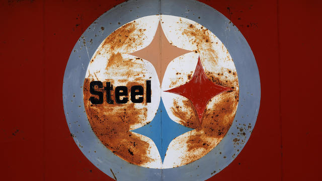 "A rusty U.S. Steel ""Steelmark"" logo rests on the side of a steel business in Peoria"