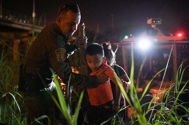 A U.S. Border Patrol agent helps asylum-seeking migrant families unload from a U.S. Border Patrol riverine unit in Hidalgo