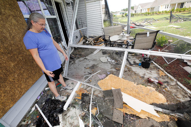 Cathy McCabe stands next to remnants of her damaged house after a tornado spawned by Hurricane Dorian ripped through Carolina Shores