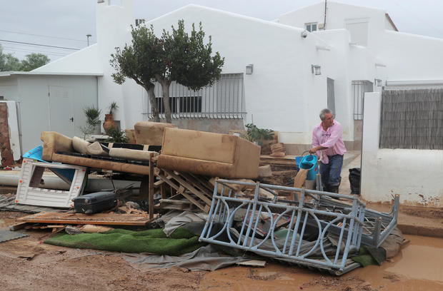 A man cleans an entrance to a house next to damaged furniture after flooding caused by torrential rains in San Javier