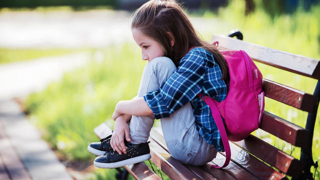 Unhappy schoolgirl sitting in the park. Education, lifestyle concept