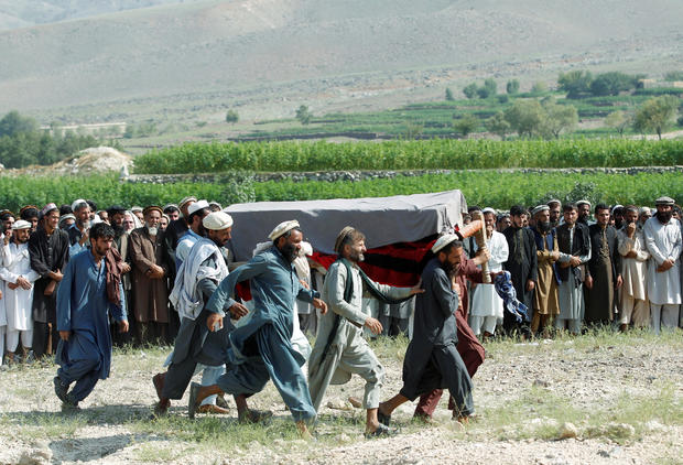 Men carry a coffin of one of the victims after a drone strike, in Khogyani district of Nangarhar province, Afghanistan