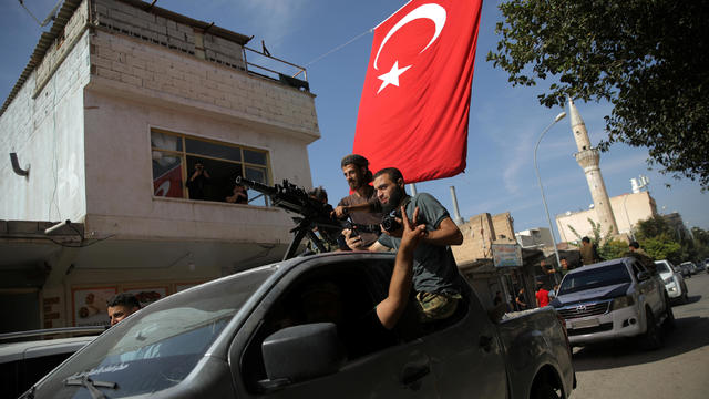 Turkish-backed Syrian rebels drive on a street in the Turkish border town of Akcakale in Sanliurfa province
