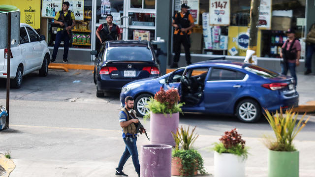 "Cartel gunmen are seen outside during clashes with federal forces following the detention of Ovidio Guzman, son of drug kingpin Joaquin ""El Chapo"" Guzman, in Culiacan"