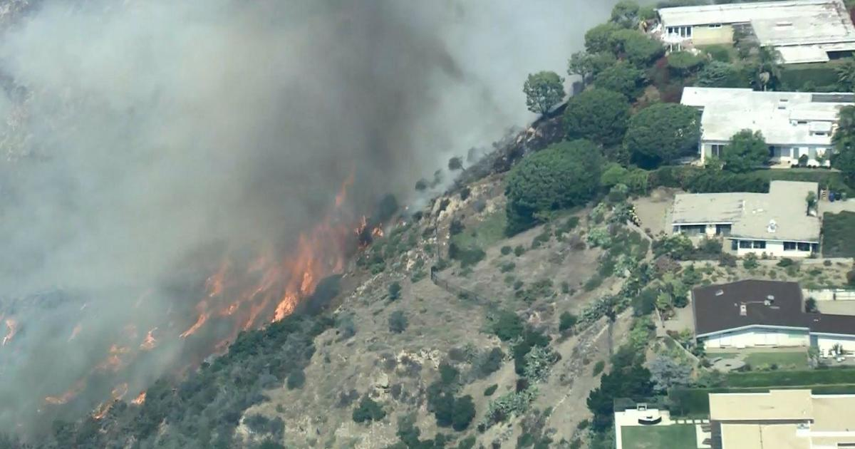 Fast-moving brush fire threatens homes in Pacific Palisades