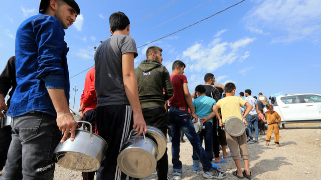 Syrian displaced families, who fled violence after the Turkish offensive in Syria, stand in queue to get their food from Barzani charity at a refugee camp in Bardarash on the outskirts of Dohuk