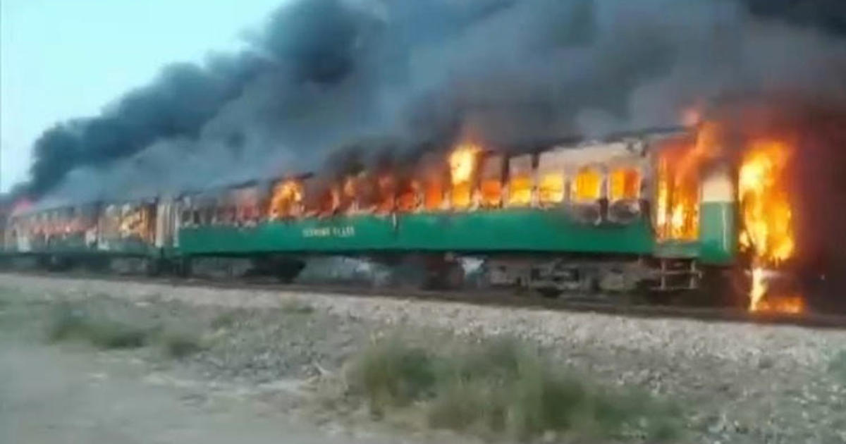 Fire sweeps through three cars of moving train in Pakistan, killing scores