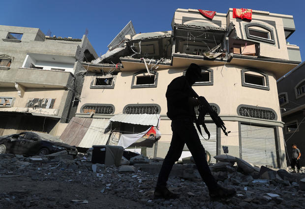 Palestinian militant walks past the home of Islamic Jihad field commander Baha Abu Al-Atta after it was hit by an Israeli strike that killed him in Gaza City