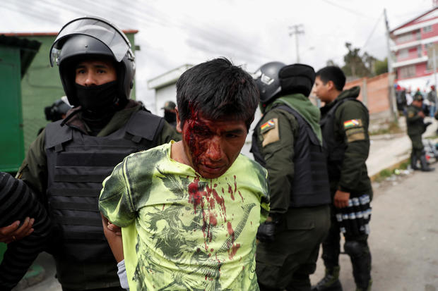 A police officer detains an injured man during clashes between supporters of Bolivian President Evo Morales, who announced his resignation on Sunday, and opposition supporters in La Paz