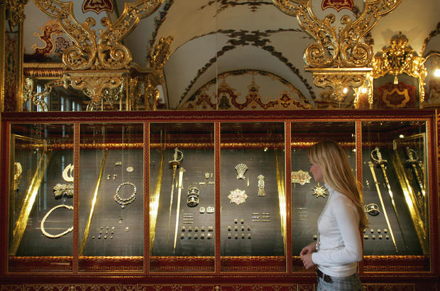 A woman looks at precious objects expose