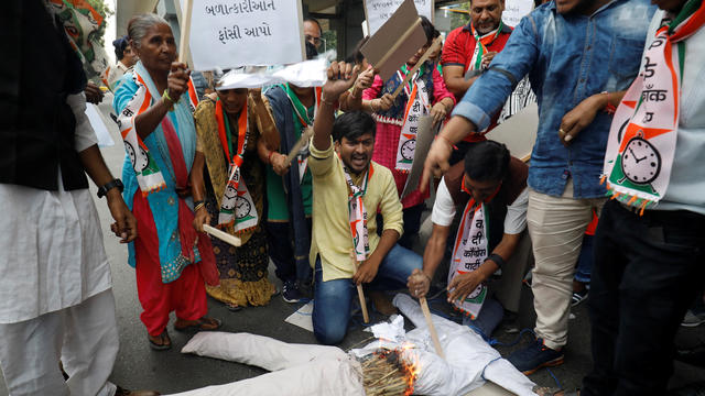 Supporters of India's main opposition Congress party burn an effigy as they shout slogans during a protest against the alleged rape and murder of a 27-year-old woman, in Ahmedabad