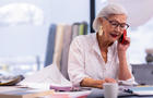 Enchanting well-groomed aging boss speaking on the phone in office.