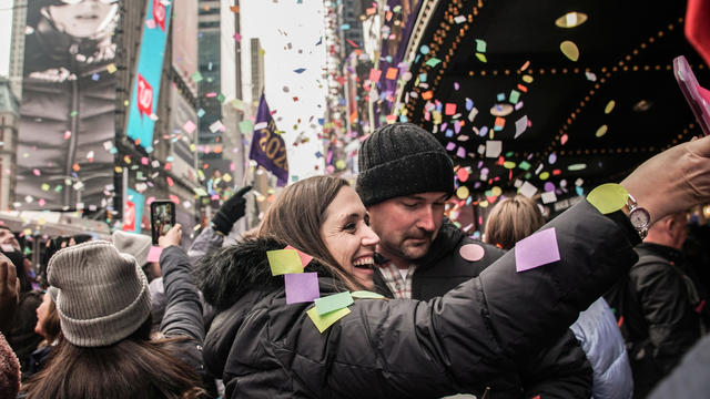 People take a picture of confetti as it's thrown from the Hard Rock Cafe marquee as part of the annual confetti test ahead of the New Year's Eve ball-drop celebrations in Times Square in New York City December 29, 2019.