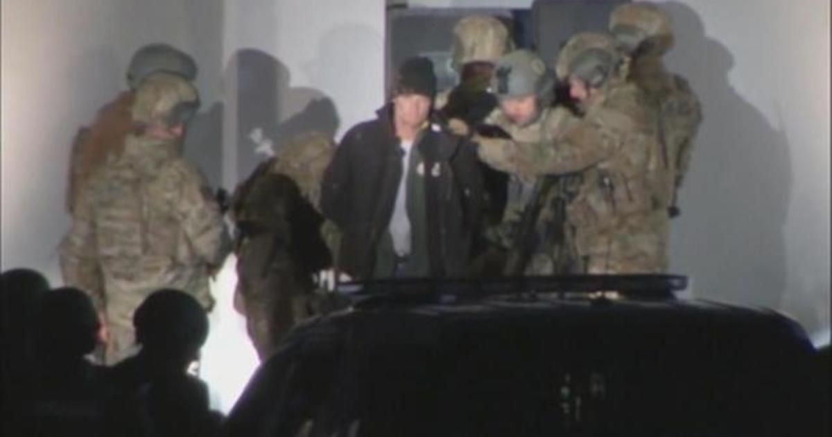 Alleged bank robber who held a woman hostage surrenders to police after 6-hour standoff