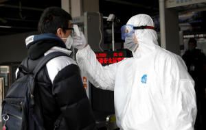 A health worker in a protective suit uses a thermometer to check the temperature of a man entering Beijing's Xizhimen subway station as China is hit by an outbreak of coronavirus January 27, 2020.