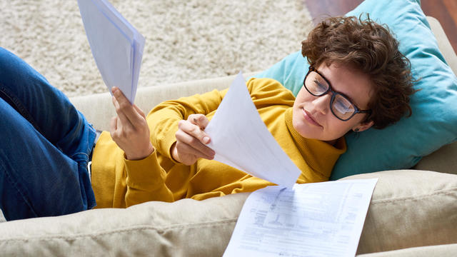 Beautiful woman lying on sofa and analyzing papers