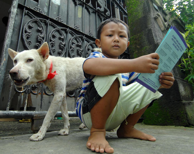 A child holds his dog's certificate afte