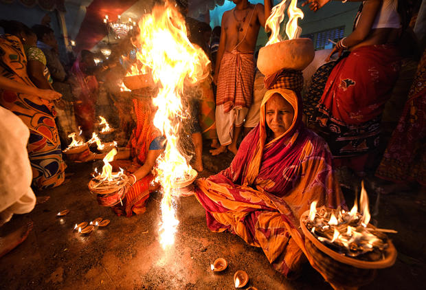 Hindu women are seen seated with burning fire pots on their
