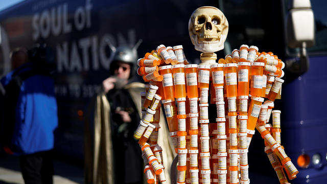 A sculpture made out of opioid pill bottles is set up next to Democratic presidential candidate and former Vice President Joe Biden's campaign bus in Somersworth
