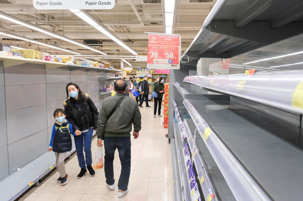 Customers wear masks as they walk past empty toilet paper shelves at a supermarket, following the outbreak of a new coronavirus, in Hong Kong