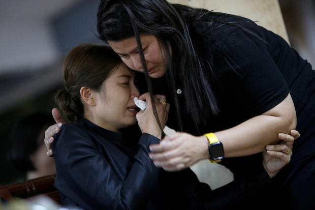 A mother of Ratchanon Karnchanamethee, who died in a mass shooting, cries duirng his funeral at a temple in Nakhon Ratchasima